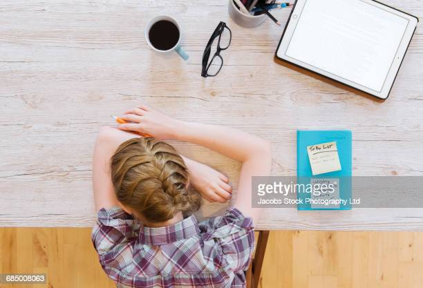 Tired Caucasian woman resting head on wooden table