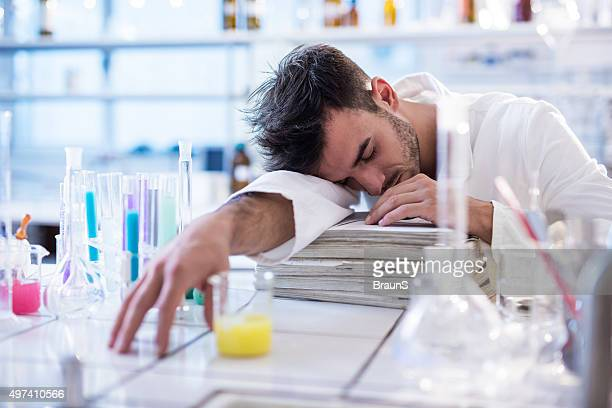 Tired chemist taking a nap in a laboratory.