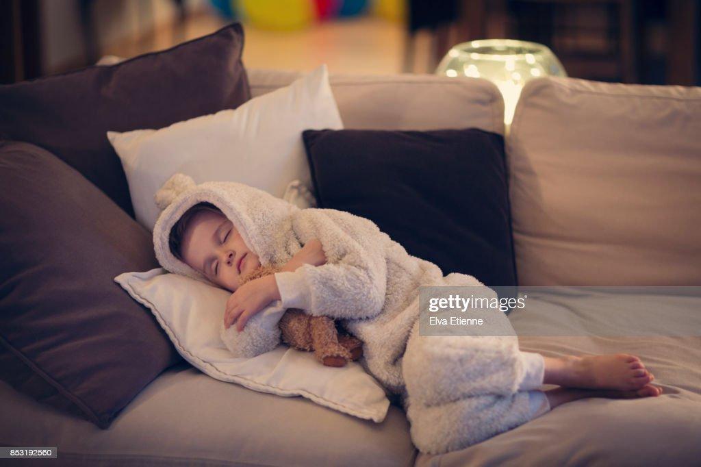 Tired child asleep on a sofa with teddy bear : Stock Photo