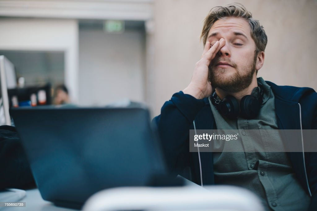 Tired computer programmer rubbing eyes while sitting in office : Stockfoto