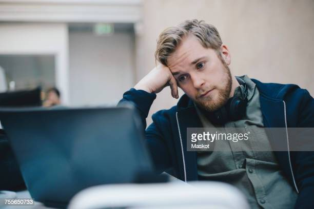 tired computer programmer using laptop in office - head in hands stock pictures, royalty-free photos & images