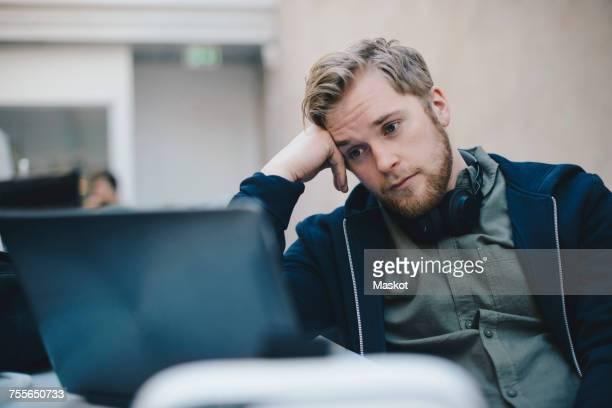 tired computer programmer using laptop in office - hoofd in de handen stockfoto's en -beelden