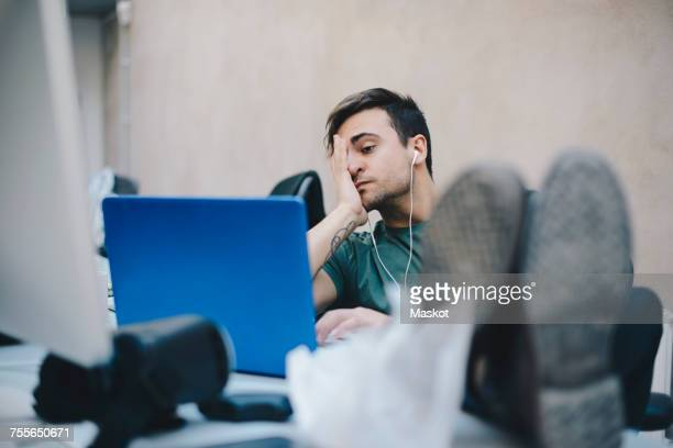 Tired computer programmer using laptop while sitting with feet up at desk in office