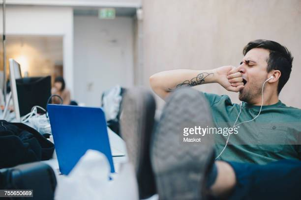 tired computer programmer yawning while sitting with feet up at desk in office - yawning stock pictures, royalty-free photos & images
