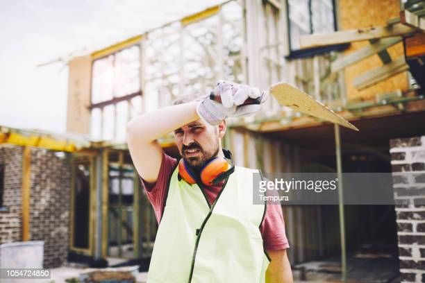 tired constructions industry worker wiping sweat. - forehead stock pictures, royalty-free photos & images