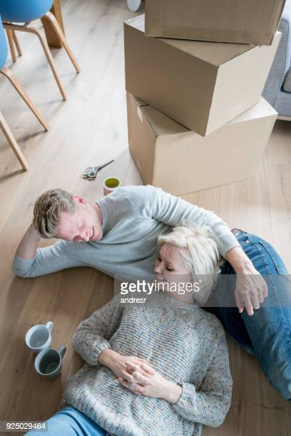 tired couple lying down on the floor after packing boxes but looking very happy and smiling - heterosexual couple photos stock photos and pictures
