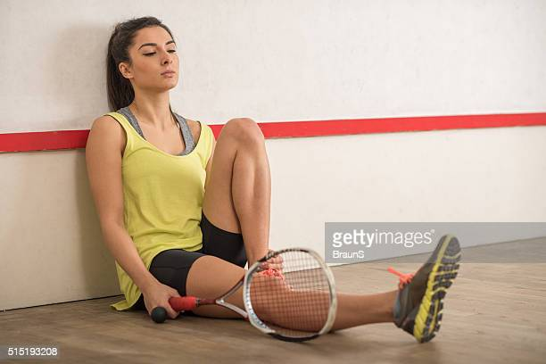 Tired female athlete taking a break from squash game.