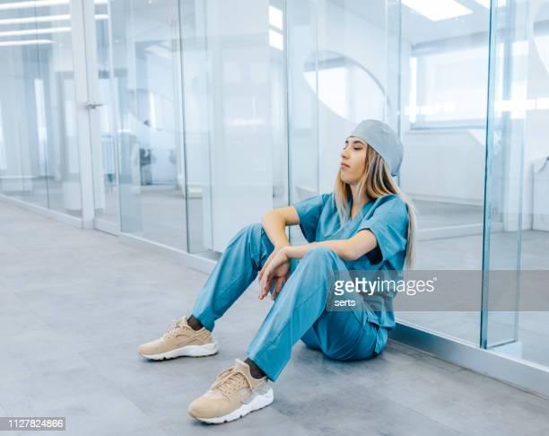 moe van vrouwelijke medische professional nemen pauze in ziekenhuis corridor - zuster stockfoto's en -beelden