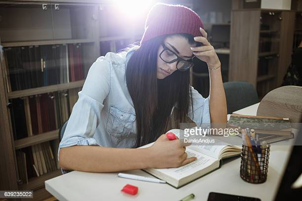 tired female student highlighting a book for exam - highlights stock pictures, royalty-free photos & images