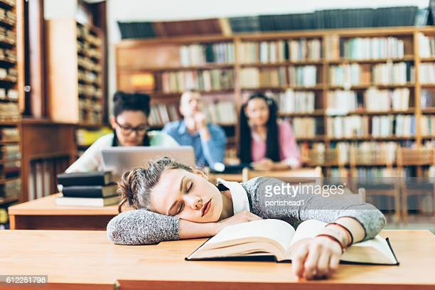 Tired female student sleeping at library