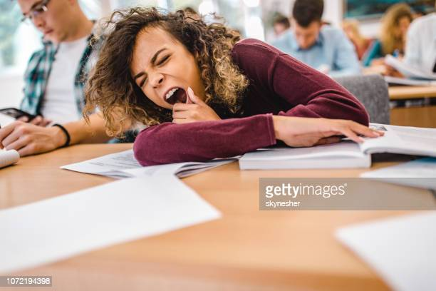 tired female student yawning on a class in the classroom. - yawning stock pictures, royalty-free photos & images