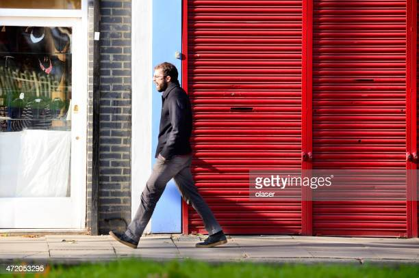 tired, freezing man walking on early london street - fast shutter speed stock photos and pictures