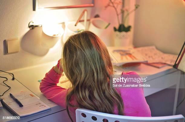 Tired girl doing homework in her room.