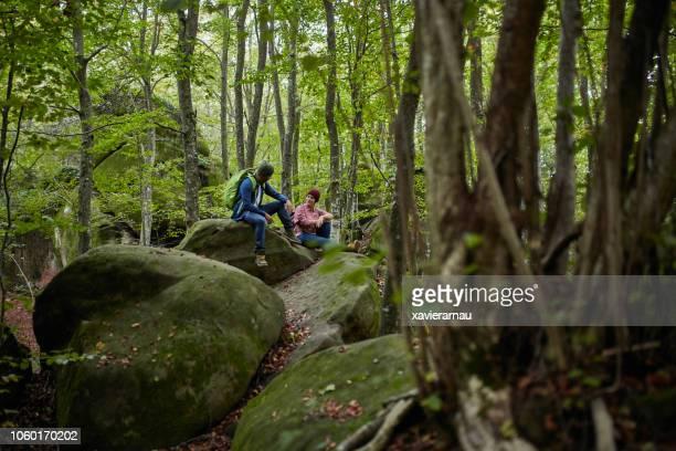 los excursionistas cansados en musgo cubren piedras en bosque - turismo ecológico fotografías e imágenes de stock