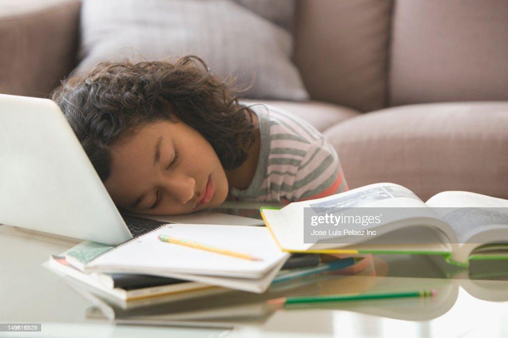 Tired Hispanic girl sleeping on laptop : Stock Photo