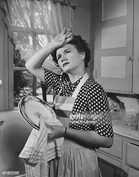 Tired Housewife Thinking And Holding Plates In Kitchen