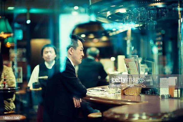 Tired Japanese salaryman waiting at the bar in a beer garden in Shibuya, Tokyo.