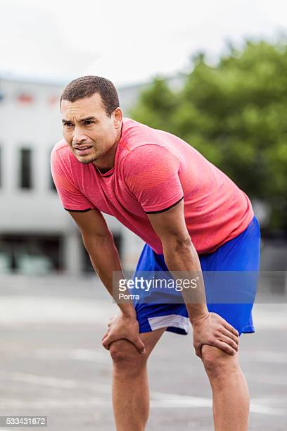 Tired jogger standing with hands on knees