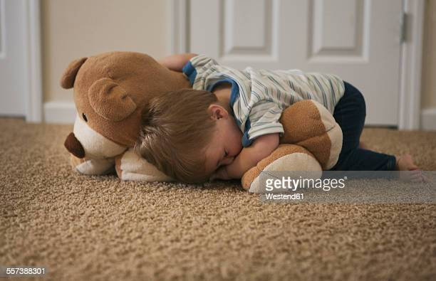 tired little boy sleeping on the floor with bear - dormir humour photos et images de collection