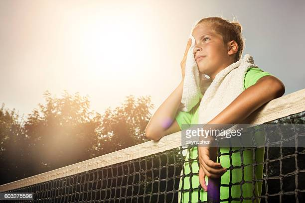 Tired little tennis player wiping sweat after sport training.