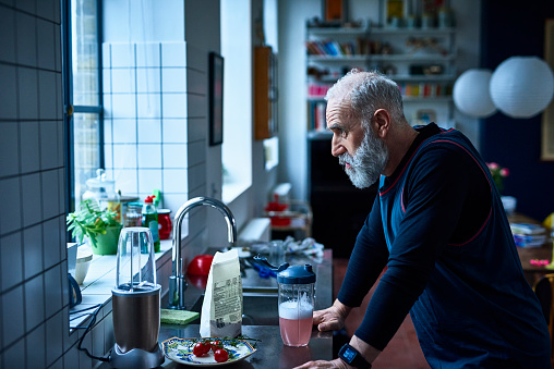 Tired looking senior man leaning on kitchen counter with sports drink - gettyimageskorea