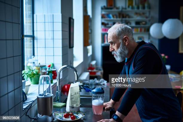 tired looking senior man leaning on kitchen counter with sports drink - derrota imagens e fotografias de stock