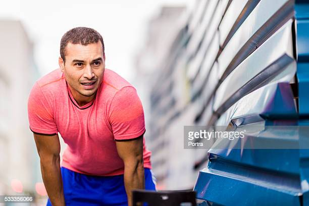 Tired male jogger bending by metal wall