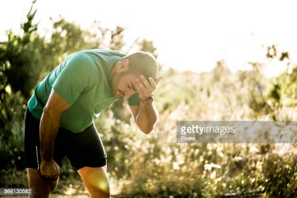 Tired male jogger bending in forest