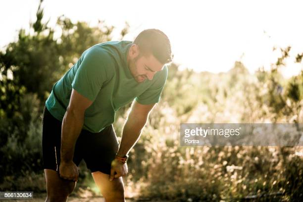 Tired male runner bending in forest