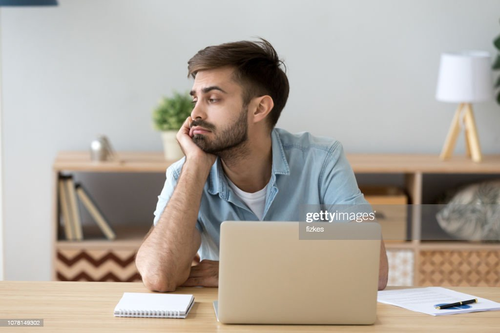 Tired man distracted from computer work lacking motivation : Stock Photo