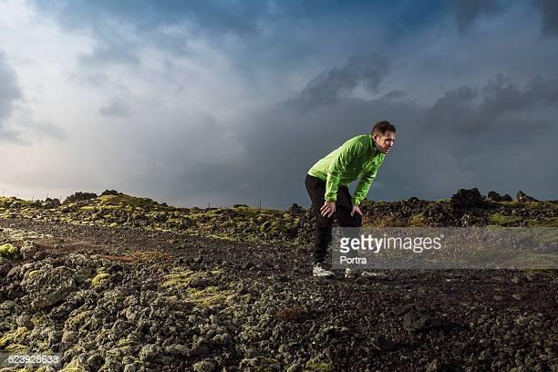 Tired man in sportswear standing on arid landscape
