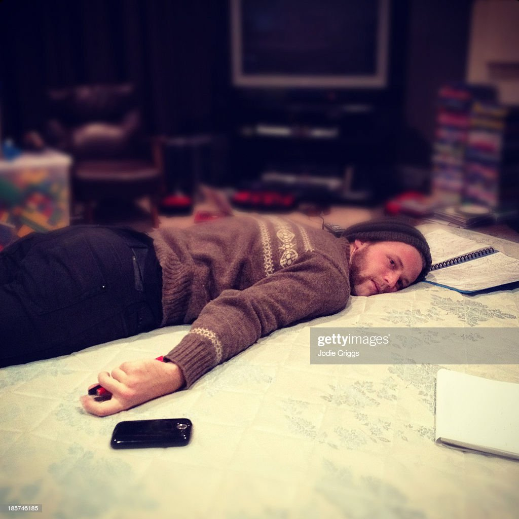 Tired Man Laying On His Stomach On The Floor Stock Photo