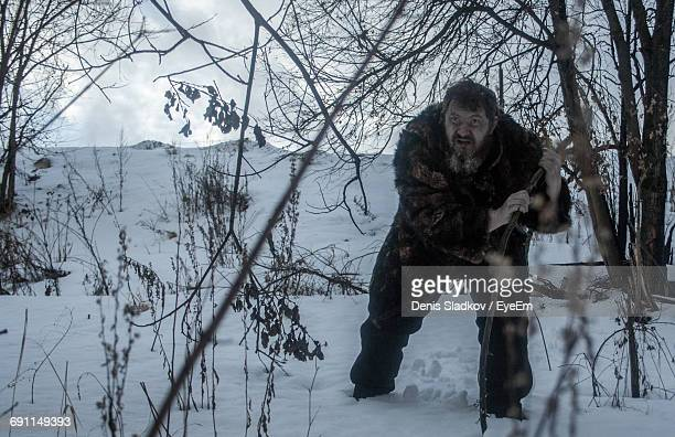 Tired Man Leaning On Bare Tree On Snowfield