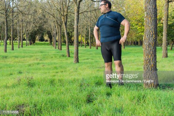 Tired Man Resting While Jogging On Grassy Field