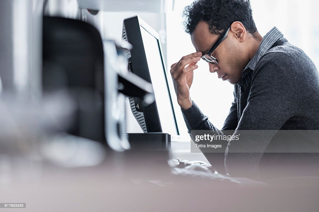 Tired man sitting in office : Stock Photo