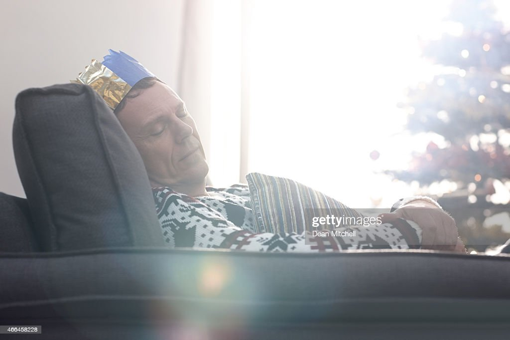 Tired man sleeping on the sofa after Christmas day : Stock Photo
