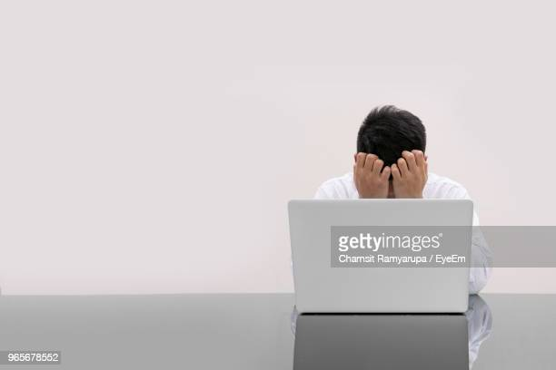 Tired Man With Laptop Sitting Against White Background