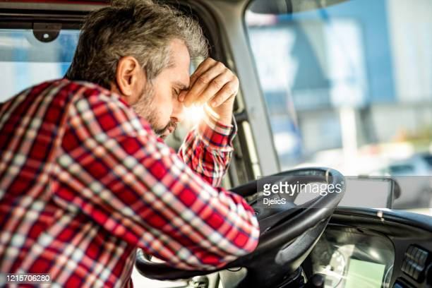 tired mature truck driver waiting in traffic and contemplating about job problems. - tired stock pictures, royalty-free photos & images