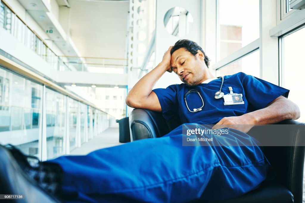 Tired medical professional sleeping in hospital lounge : Stock Photo