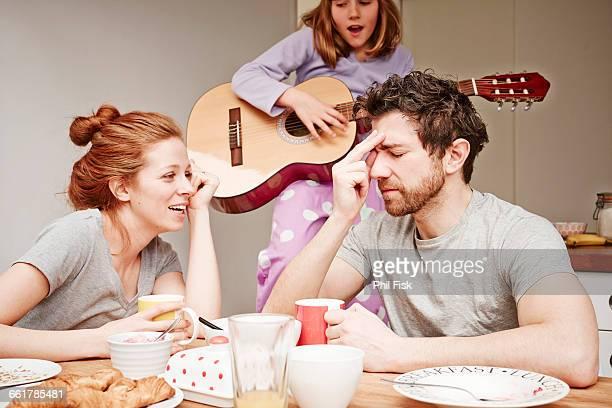 tired mid adult parents at breakfast table whilst daughter plays guitar - manos a la cabeza fotografías e imágenes de stock