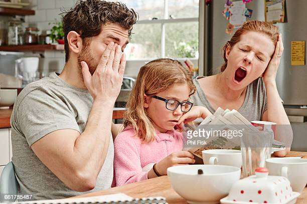 Tired mid adult parents at breakfast table whilst daughter reads newspaper