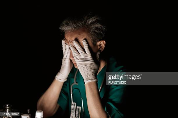 Tired middle aged surgeon covering face with hands