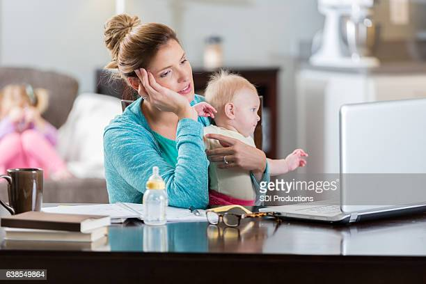 Tired mom studies for college exam while holding baby girl