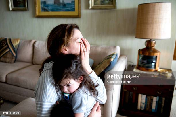 tired mother and toddler hugging inside - fatigue stock pictures, royalty-free photos & images