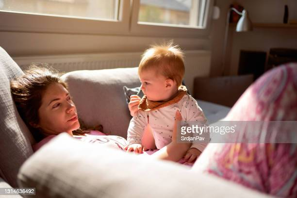 tired mother holding her baby son - tired stock pictures, royalty-free photos & images