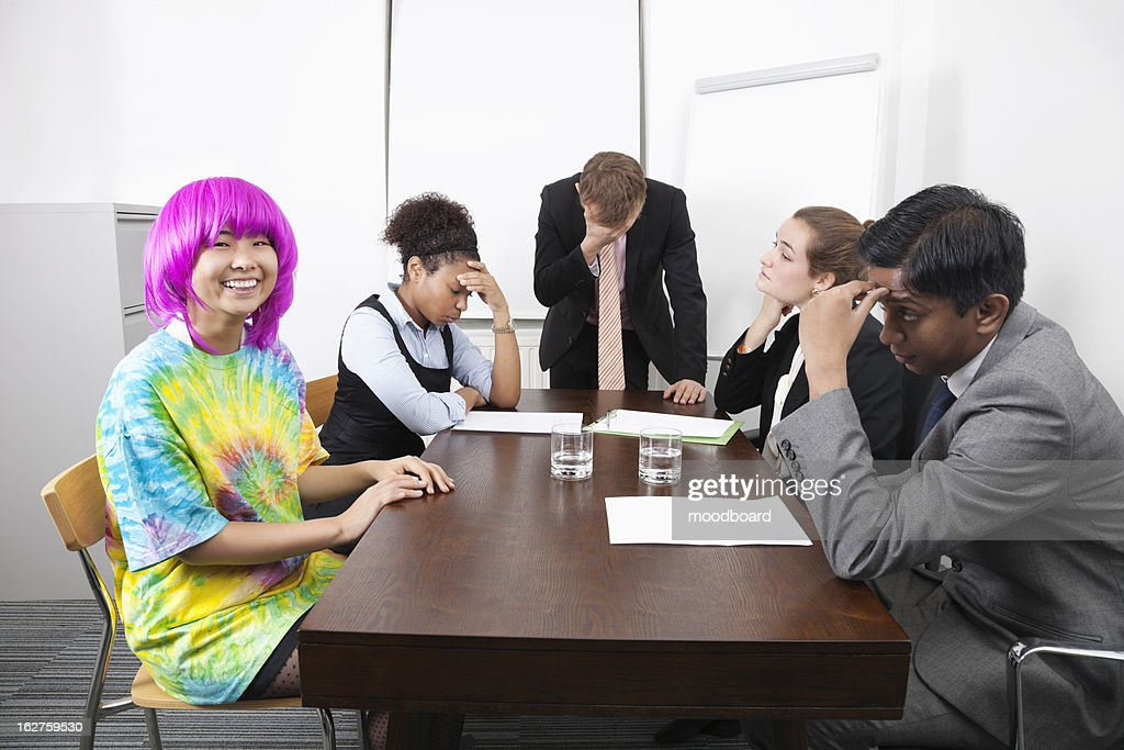 Tired multiethnic businesspeople with colleague in pink wig at meeting : Stock Photo