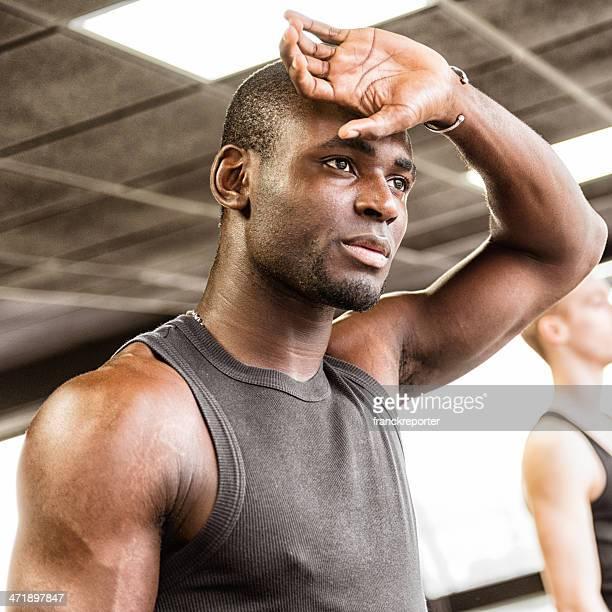 Músculos cansados hombre en el gimnasio.