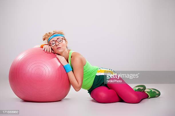Tired nerdy fitness girl sleeping on pilates ball