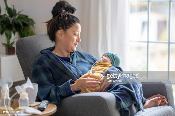 tired new mother holding her baby - breast pump stock pictures, royalty-free photos & images