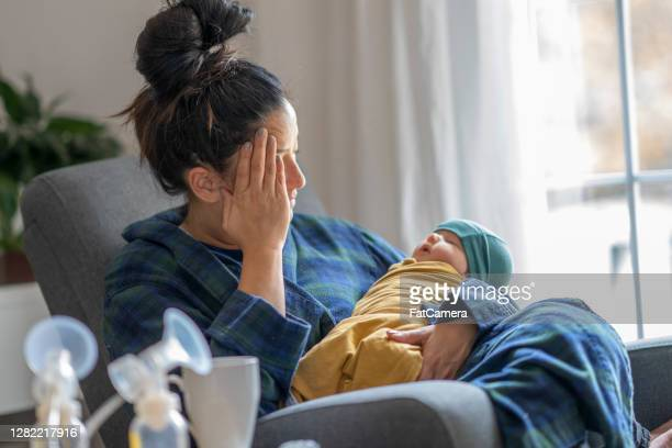 tired new mother holding her baby - fatcamera stock pictures, royalty-free photos & images